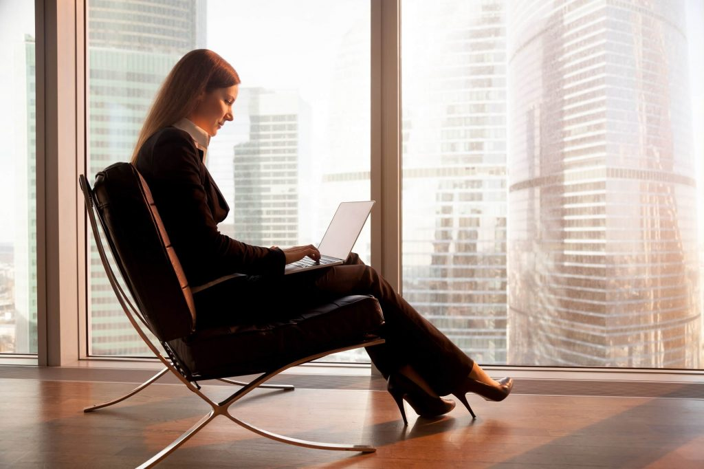 Businesswomen in a chair reading from her laptop