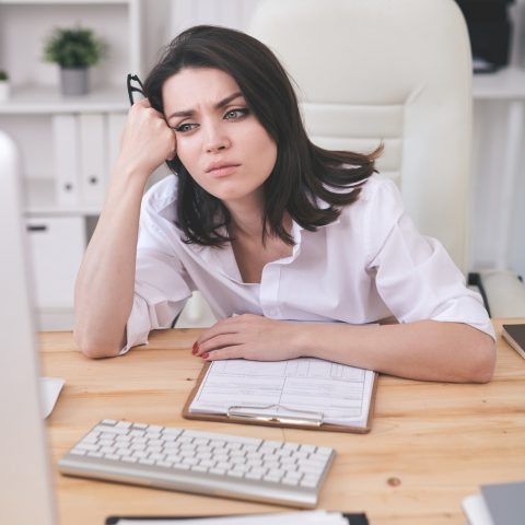 Young tired or annoyed businesswoman waiting for online page uploading