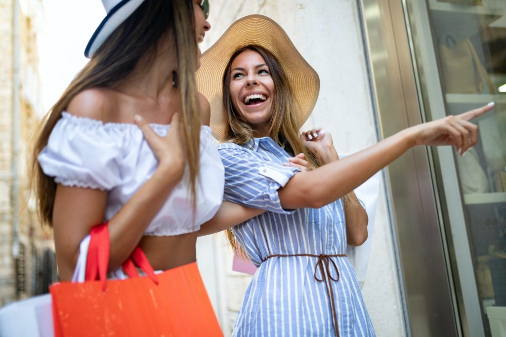 Happy friends shopping and traveling during summer