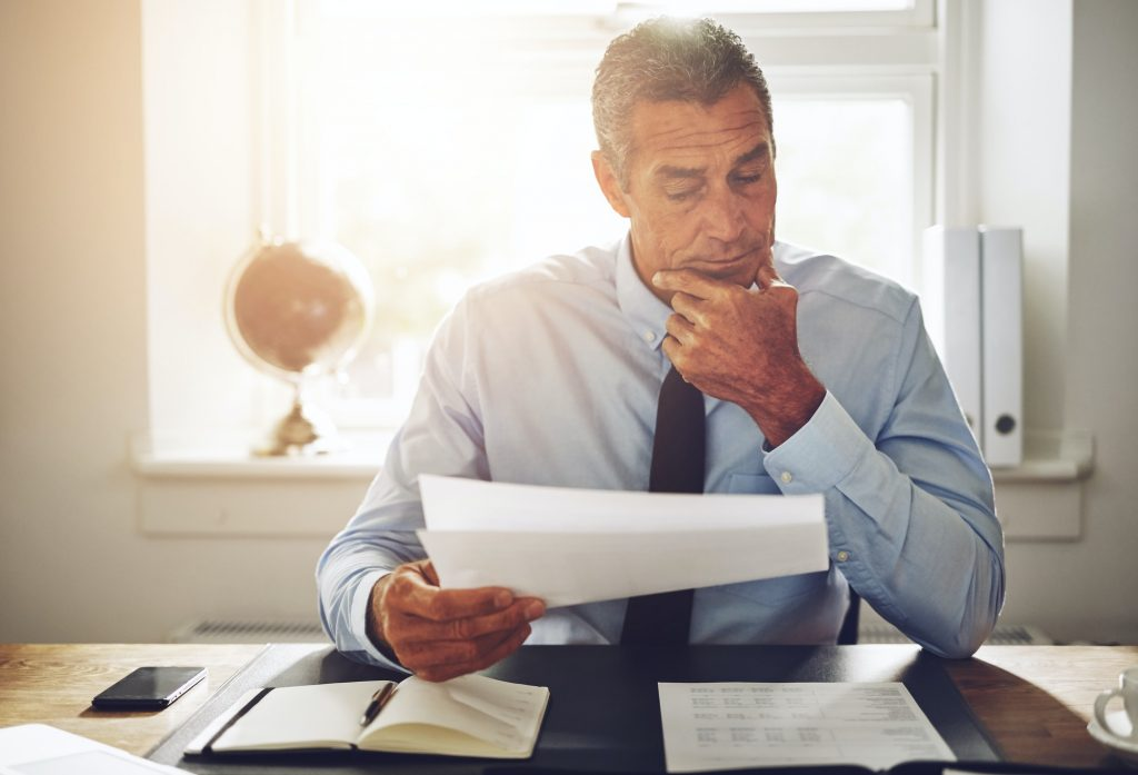 Mature businessman reading through documents at an office desk