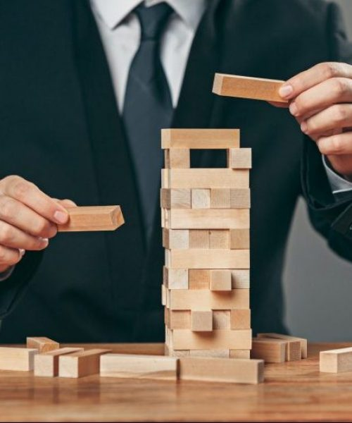 Man and wooden cubes on table. Risk Management concept