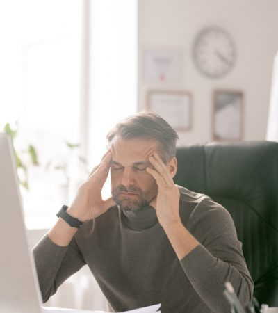 Mature tired businessman with his eyes closed trying to concentrate by workplace