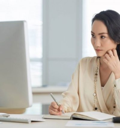 women at computer trying to figure women at computer trying to figure out her financial statements